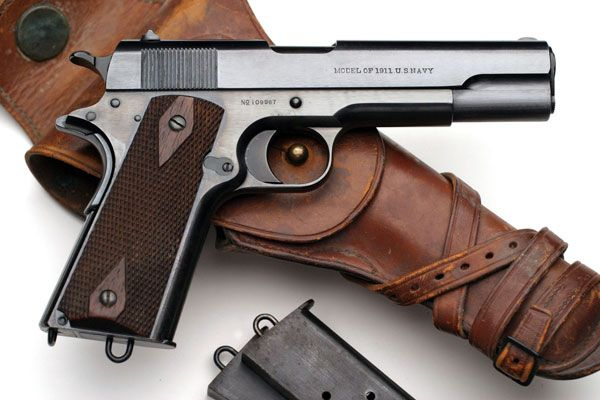 Colt Model of 1911 U.S. NAVY Serial Number 109967 - Manufactured in 1915 and part of a 500 gun Navy contract order.  Gun is pictured with original M1912 holster and two spare lanyard loop magazines all of which accompanied the pistol.