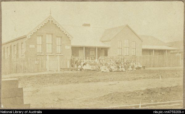 View of school girls and teachers outside brick and weatherboard Hill End Public School with corrugated iron roof and paling fence, Tambaroora Street, Hill End, New South Wales, ca. 1872 [picture]. Part of B.O. Holtermann archive of Merlin and Bayliss photographic prints of New South Wales and Victoria [picture]. between 1872 and 1888. From National Library of Australia http://nla.gov.au/nla.pic-vn4759209