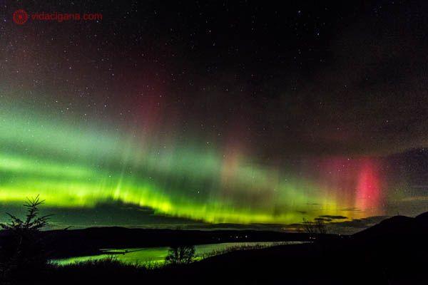 A Aurora Boreal vista de Inverness, nos Highlands, as Terras Altas da Escócia. O céu aparece pintado de luzes roxas, verdes e amarelas, é a aurora boreal em seu total esplendor. A foto é noturna, com o céu estrelado e um loch refletindo a cor verde abaixo.