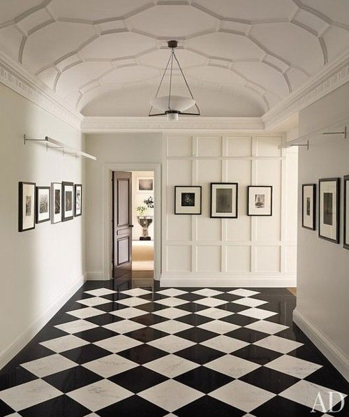 The coffered and detailed ceiling; the paneling at the rear wall.  Both add detail balanced by the monochrome color scheme and minimal gallery elements.