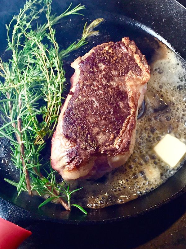 Cast Iron Seared Strip Steak with Herbs and Butter - 2 thick inches of cast iron seared, butter basted, prime, beefy goodness… Forget that over priced steak house - this is all the beef you're ever gonna need.  - theoptimalistkitchen.com