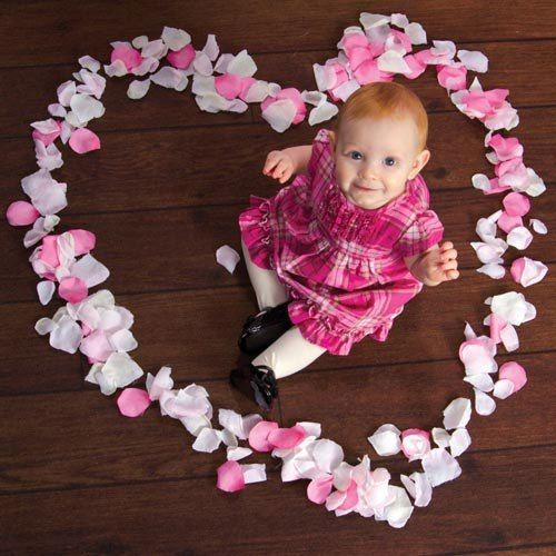 baby surrounded by Pink and white petal in a heart shape