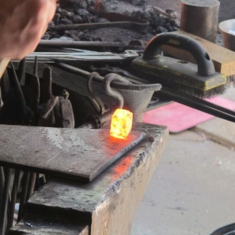 Upsetting the cube in a header plate/monkey tool.  The cube will become the ball end on one of the andirons