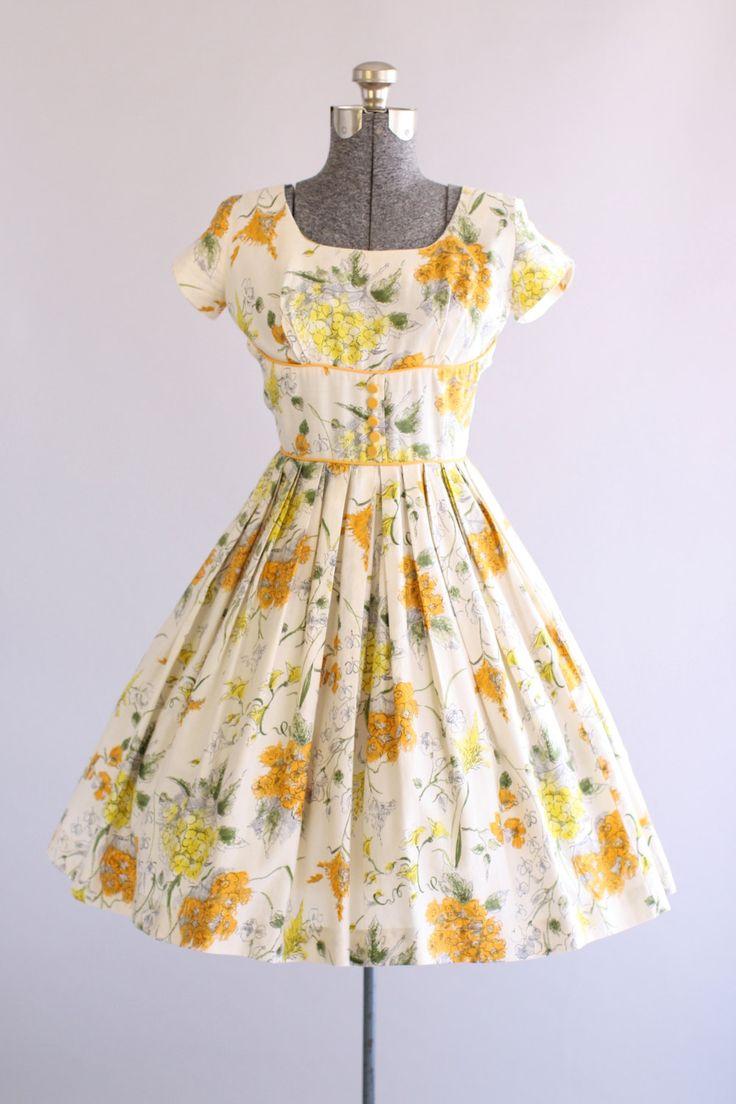 Deze jaren 1950 katoenen jurk beschikt over een prachtige oranje, gele en groene bloemenprint bovenop een witte achtergrond. Korte mouwen. De