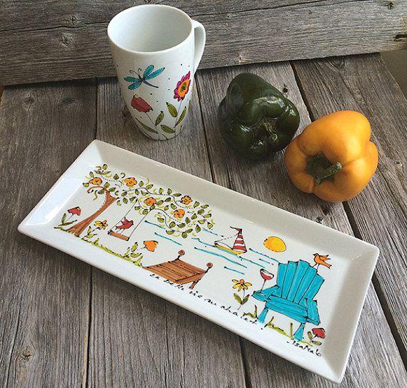 Assiette porcelaine rectangle • Chaise Adirondack turquoise et paysage avec bord de leau et voilier 12 x 5 peint à la main par lartiste peintre Isabelle Malo  Je les peints une à une, à la main donc elles sont tous uniques. Les traits et les couleurs peuvent un peu varier, ce qui en fait leurs charmes !  Le dessin et les couleurs peuvent un peu varier selon chaque pièce.  Il est recommandé de laver à la main. Ne pas mettre au lave-vaisselle. Peut aller au micro-ondes.  Pour livraison…