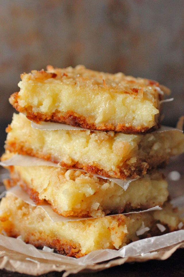 These bars have a cake mix crust and a cream cheese lemon filling. Sweetened coconut flakes add texture. #desserts #bars
