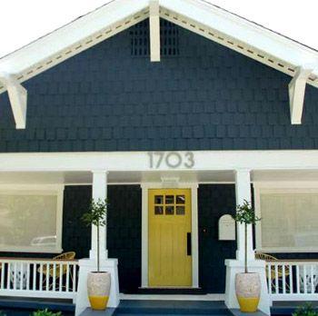Steel-blue wood, crisp white trim and a yellow door that pops.