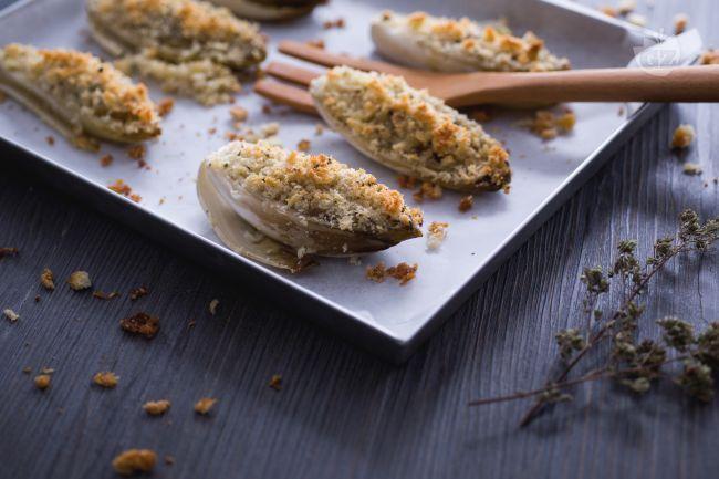 L'indivia belga gratinata è un semplice e gustoso contorno invernale arricchito da una croccante panatura aromatizzata all'origano.