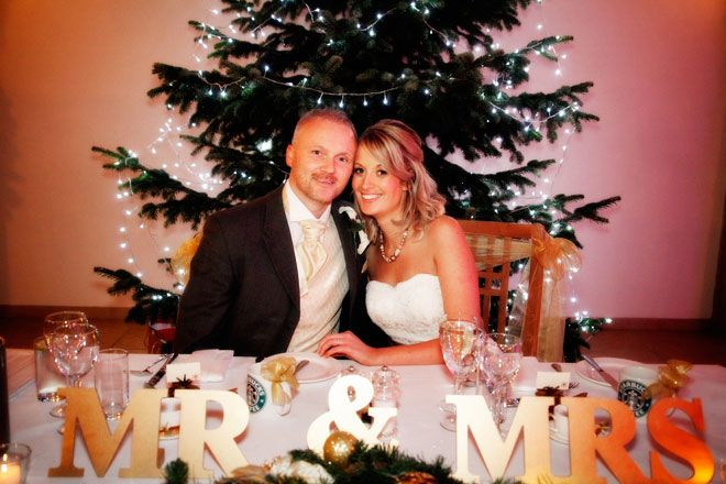 Bride and groom in front of a Christmas tree at a Rivervale Barn | www.allabouttheimage.co.uk