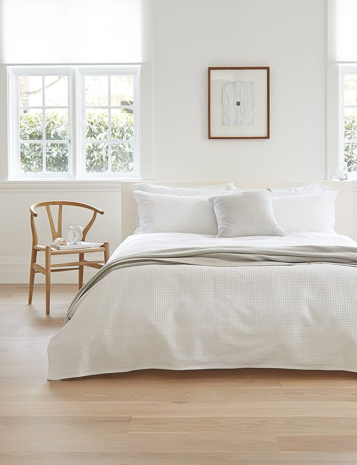 Elegant bed linen and satin and cotton bedding and a beautiful bent arm chair with white walls and no headboard. Simple, understated and elegant bedroom.