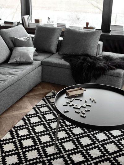 Salon aux teintes grises et noires avec une table basse adaptable