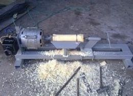 Wood Lathe - Homemade wood lathe constructed from tubing, bar stock, steel plate, and a surplus washing machine motor.