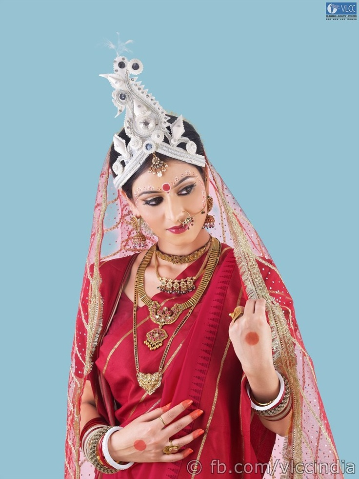 The Bengali look stuns with eyes that are enhanced using the base color of the sari and contoured with a color two shades deeper. Lined with deep kohl and false lashes, they sparkle. The lips are highlighted with high sheen while the forehead is decorated with intricate designs of Chandan. The hair is gathered into a bun, covered with a veil and adorned by a traditional Mukut.