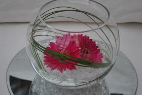 Glass fish bowl centerpiece with clear gel, 3x pink gerberas and bear grass on a round mirror plate. Very simple but effect. Also lo...