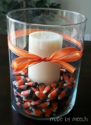 Glass filled with candle and candy corn. Simple.  Then maybe a piece of…