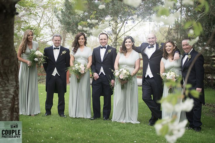 The bridal party at a gorgeous cherry blossom tree. Weddings at Druids Glen Resort by Couple Photography.