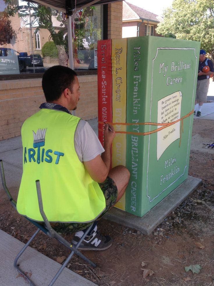 Artist Adam Long at work on Queanbeyan Library's power box.