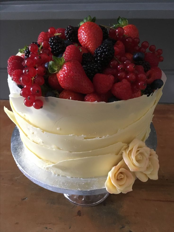 White Chocolate and raspberry cake. Wrapped I white chocolate and decorated with red fruits.