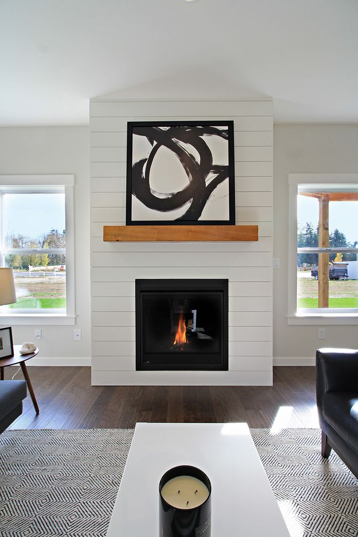 White shiplap fireplace surround with wood mantle ...