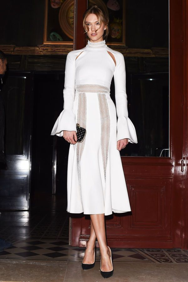 Karlie Kloss rocks a turtle-neck and fluttery sleeves in an elegant white maxi dress.