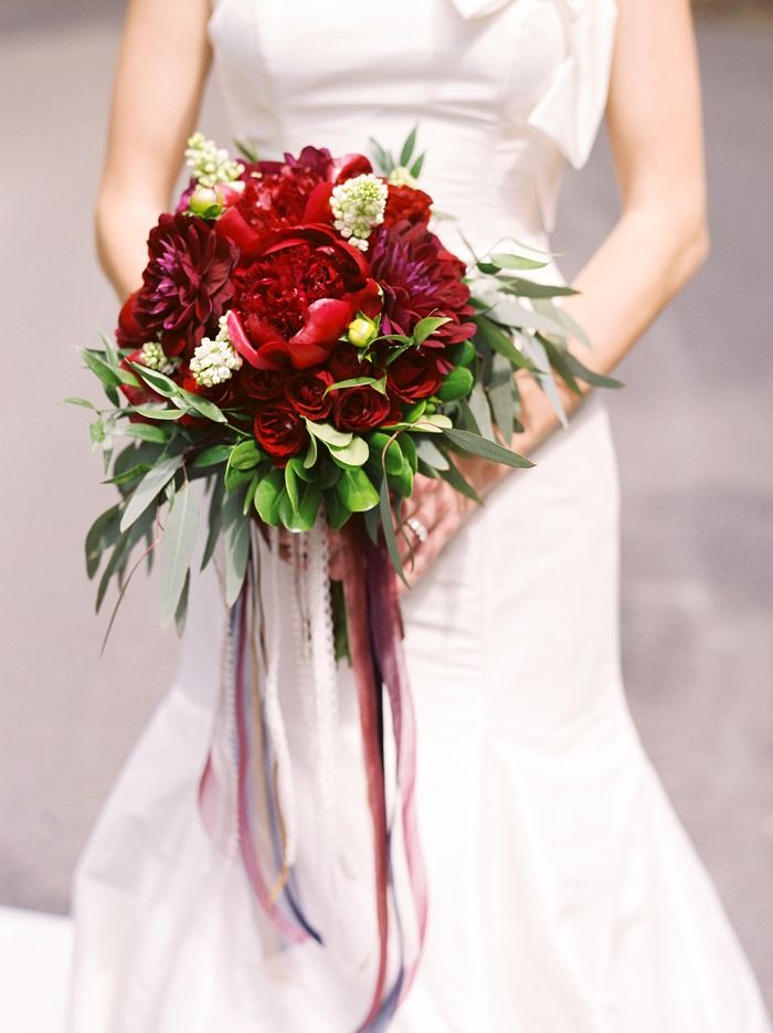 Gorgeous red bridal bouquet by garden gate