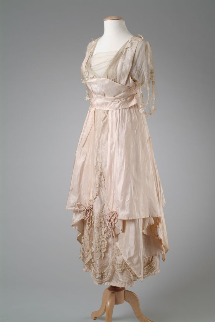 Side Front: SILK TAFFETA EVENING GOWN, 1914 1914 Pink silk taffeta evening gown with a pannier effect on the hip, and trimmed with machine embroidered net. Accented with crushed cording flower trim. This garment was owned by Matilda Dodge Wilson (October 19, 1883 – September 19, 1967),who was the wife of John Francis Dodge (October 25, 1864 – January 14, 1920), co-founder of the Dodge Motor Car Company in Detroit, Michigan. Wayne State University Library Digital Collection