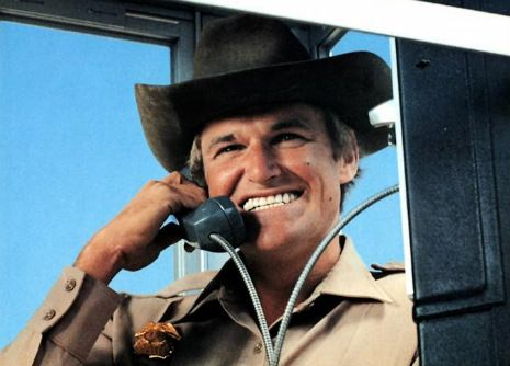 Charles Napier wearing cowboy hat and shit-eating grin