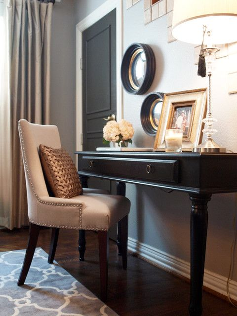 Office space with black desj, gray walls and upholstered chair.