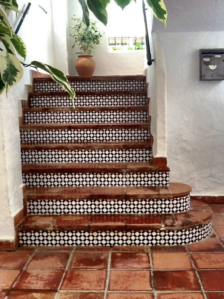 Beautiful staircase tiling adds a mexican touch when paired with the terracotta