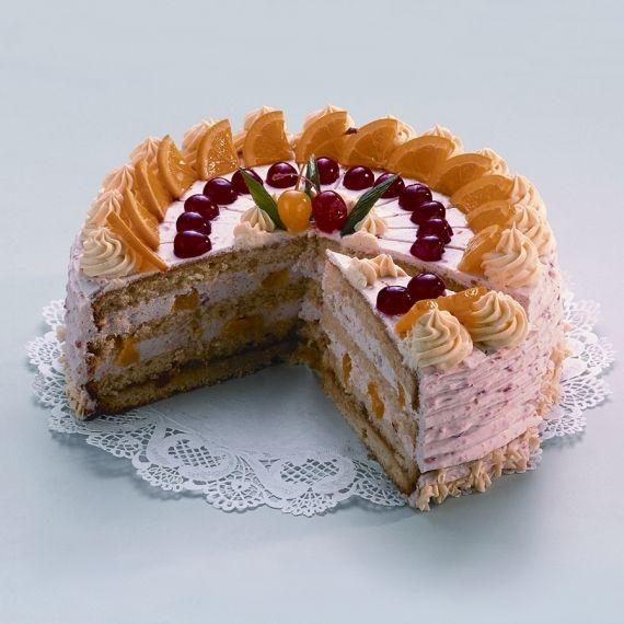 Tort Owocowy Nasączone syropem krążki ciasta biszkoptowego przekładane śmietaną ze zmiksowanymi owocami oraz kawałkami owoców. Owoce użyte do dekoracji tortu są bazą smaku.