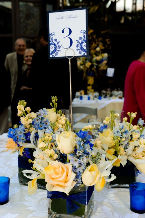 Yellow And Blue Arrangements In Clusters Of Clear Square Vases Lined With Leaves Amp A Blue Ribbon