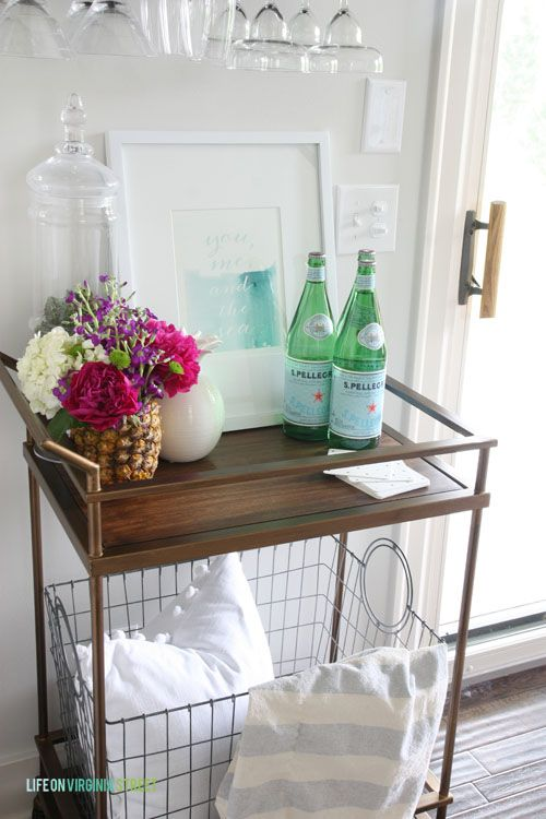 Loving this summer bar cart in this gorgeous home tour. That fresh pineapple vase with peonies and hydrangeas is on my list to make! Striped throw with pom pom pillow are also cute.