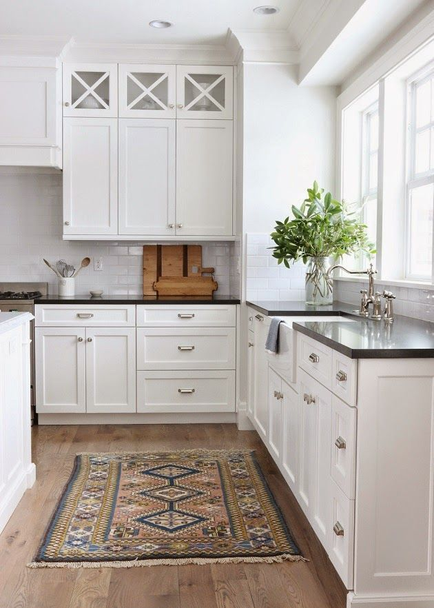 modern traditional kitchen with white cabinets, black countertops, and polished nickel fixtures