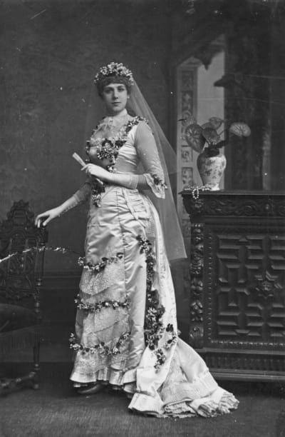 Un vestido de novia con un polisón, decorado con flores.