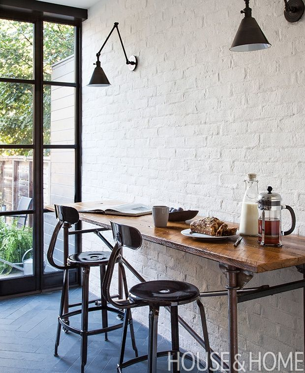 In this renovated kitchen, designer Trish Johnston maintained the cool texture of the brick veneered wall, but painted it a neutral white to conceal its flaws.    Photographer: Donna Griffith  Designer: Trish Johnston