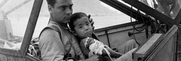 TOP 1000 | An American soldier cradles a wounded Japanese boy and shelters him from the rain in an airplane cockpit during the Battle of Saipan while waiting to transport him to a field hospital, July 1944. Photo by Peter Stackpole. | History Photo 66