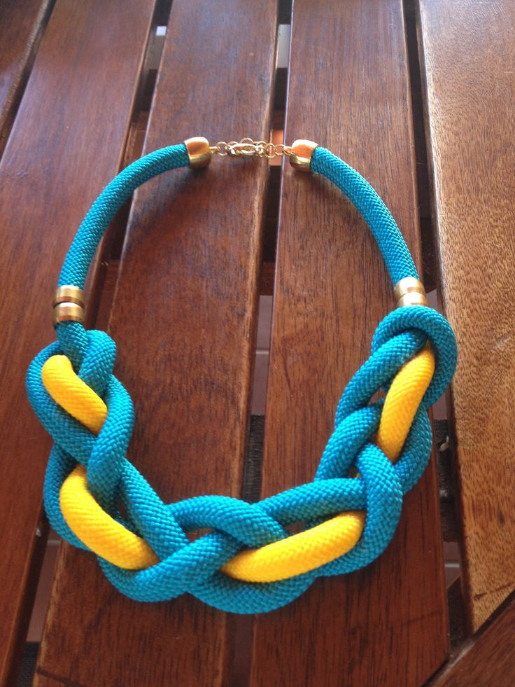 Blue/yellow rope necklace with gold details on and golden clasp.
