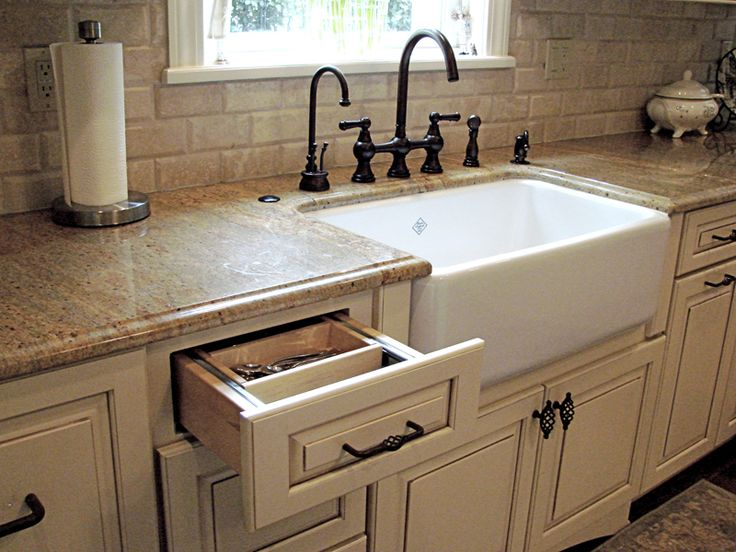 Modern farmhouse sink w/ cream cabinets & granite countertops.
