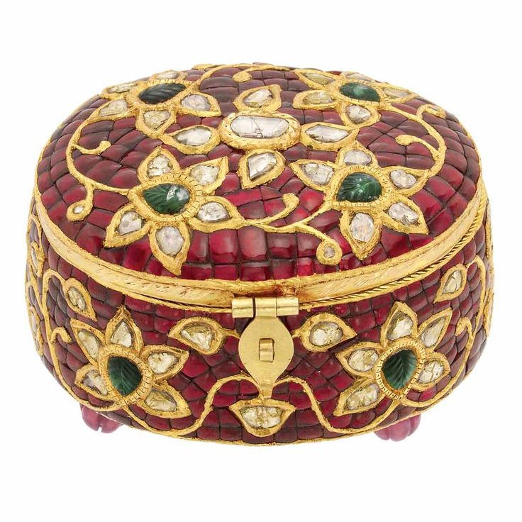 Indian High Karat Gold, Foiled-Back Stone and Gem-Set and Diamond Box. The oval gold box encrusted with red enamel plaques, set throughout with a floral design composed of 8 foiled-back carved emeralds and foiled-back diamonds, outlined in gold, supported by 4 fluted ruby bead feet, opening to reveal an oval turquoise hardstone panel inlaid with 8 pear-shaped foiled-back diamond, ruby, sapphire, cat's eye, yellow chrysoberyl, coral and split pearl, approximately 123 dwts. gross.