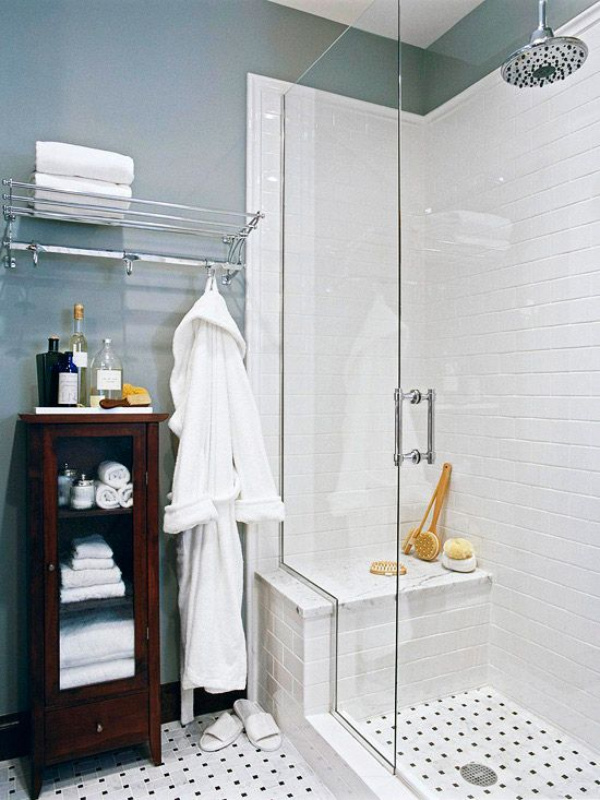 Tall, clear-glass shower doors create the illusion of more room. The white subway tile and chrome fixtures reflect light, contributing to the sense of spaciousness. Basket-weave tile covers the floor and carries into the shower for continuity.