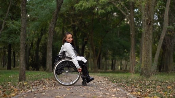 Attractive Girl on a Wheelchair Walking in the Autumn Park