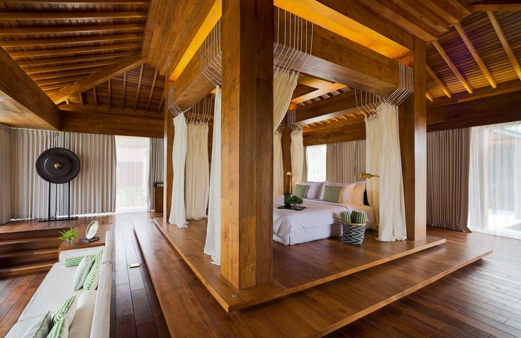 Giant canopy bed behind a sunken living room in a bungalow modeled after traditional architecture Malang East Java Indonesia [20001298]