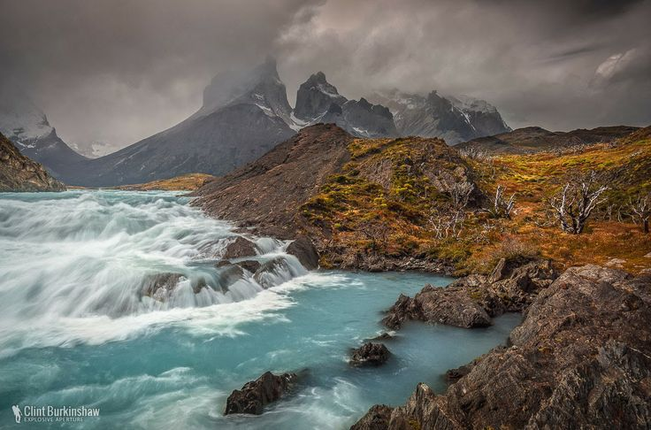 Storm over Cuernos del Paine, Patagonia, Chile  Dark storm clouds rage in the background above the majestic shaped mountains, while the extremely high gusts of wind ravage the landscape in the foreground creating quite a scene.  #SouthAmerica #Chile #TravelPhotography #LandscapePhotography #TorresdelPaine