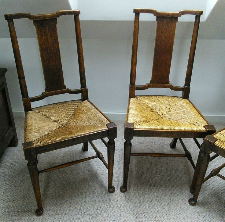 Two, of four, oak side chairs by William Morris. Retailed as The Hampton chair, it was originally designed by W.Lethaby in the office of Richard Norman Shaw for use in the Tabard Inn. See also the matching carver / open armchair.