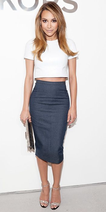 NAYA RIVERA Rivera bared her midriff at the Michael Kors fall/winter 2014 show in a look by the label: a crop top and a body-hugging denim pencil. She accessorized with a metallic clutch and neutral heels.