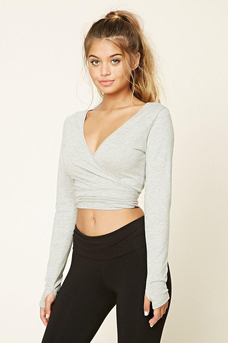 A heathered knit ballet crop top  featuring a wrapped self-tie waist, a deep V-n…