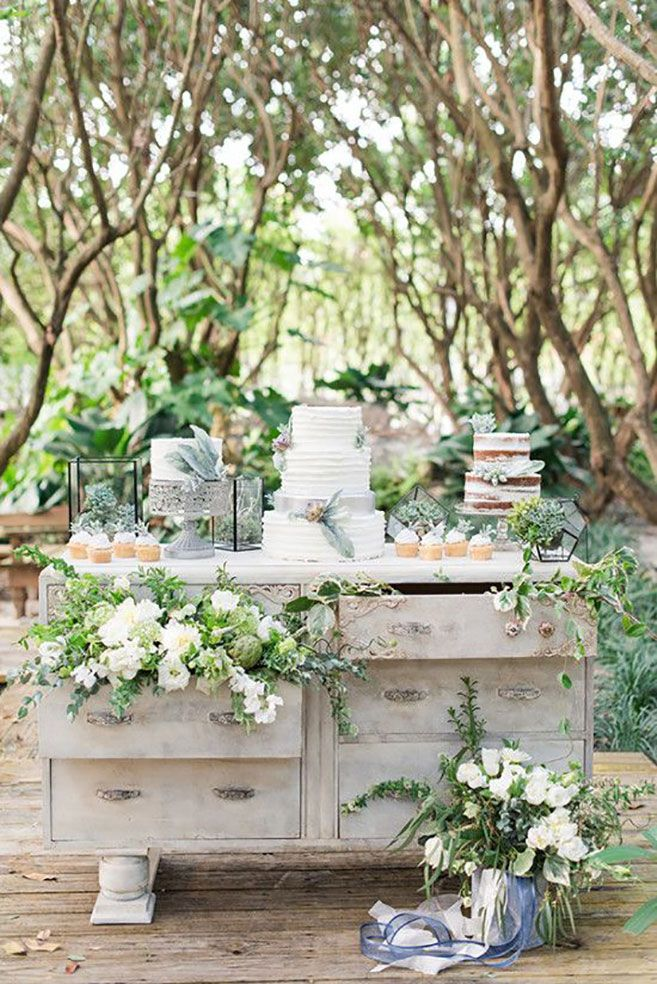For a natural-yet-vintage feel, use an antique dresser as your dessert table and fill it with plenty of lush florals for an elegant look.     Photo via  Wedding Chicks.