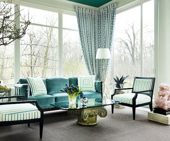 Dramatic, floor-to-ceiling windows are emphasized by the Greek key pattern draperies in this wow-worthy sunroom. The coffee table base echoes the look of a traditional Greek column. Traditional-look furniture pieces, such as the sofa and chairs, are dressed with stylish indoor-outdoor fabrics that can stand up to wear and tear.