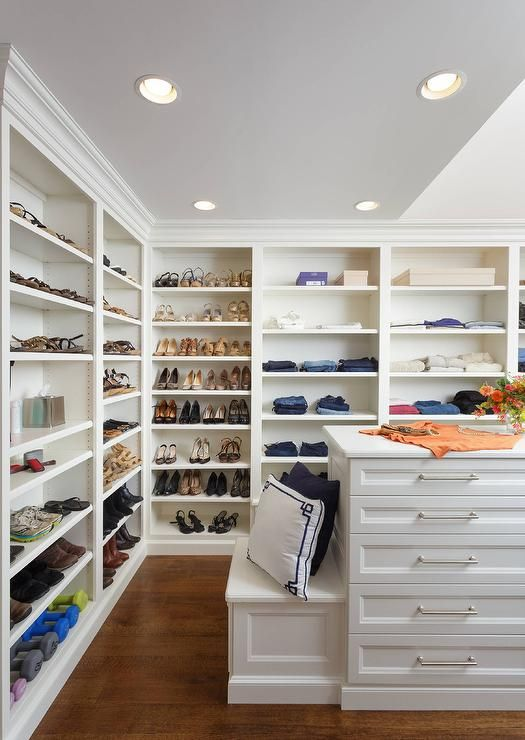 Custom walk-in closet features walls lined with floor to ceiling white modular shoe and jean shelves lit by recessed lighting and facing a white island finished with jewelry drawers adorning nickel pulls and a white drop down bench.