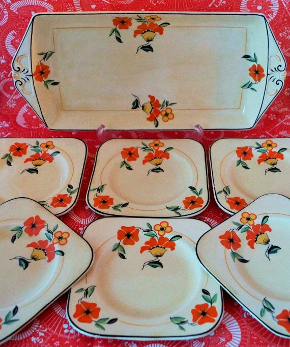 A most attractive set of sandwich plate and six side plates, in buttermilk yellow with burnt orange and yellow flowers.   c.1920